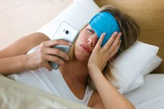 Tired young woman lying in bed pulling up sleeping mask to see what time is it at smartphone in bedroom at home. Shot of tired young woman lying in bed pulling royalty free stock photos