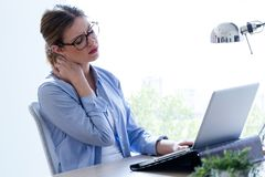 Tired young woman with neck pain using her laptop at home. Stock Photography