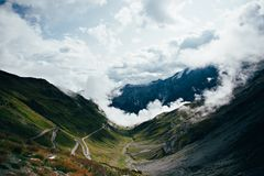 View on cloudy twisting road in mountains royalty free stock photography