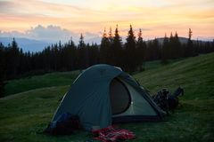 Tent on a camping site in the mountains. Shot of a tourist tent placed on top of a hill beautiful sunset on the background active sportive lifestyle travelling Royalty Free Stock Photography