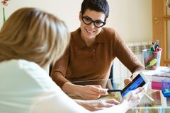 Two businesswomen talking about work and exchanging ideas with digital tablet in the office. Shot of two businesswomen talking about work and exchanging ideas royalty free stock photos