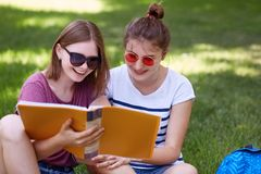 Shot of two cheerful friends have joyful looks into book, read something funny, wear sunglasses, pose against green grass backgrou. Nd, spend time after classes stock images