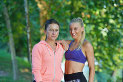 Shot of two females taking a quick break while out for a trail run using phone.  Stock Photos