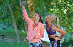 Shot of two females taking a quick break while out for a trail run using phone.  Stock Photography
