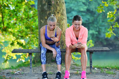 Shot of two females taking a quick break while out for a trail run using phone.  Stock Image