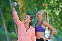 Shot of two females taking a quick break while out for a trail run using phone.  Royalty Free Stock Photos