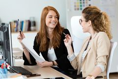 Two pretty young business woman talking and reviewing papers in the office. stock photography