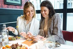 Two pretty young women using smartphone while eating in a restaurant. Shot of two pretty young women using smartphone while eating in a restaurant stock photos