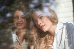 Two female friends at the cafe. Shot of two young beautiful female friends using laptop together while studying at the local cafe friendship lifestyle people Royalty Free Stock Images