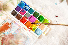 Shot of used watercolors with paintbrush on table Stock Images
