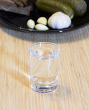 Shot of vodka and appetizer on a wooden table Stock Photo