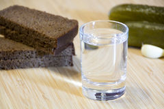 Shot of vodka and appetizer on a wooden table Royalty Free Stock Photos