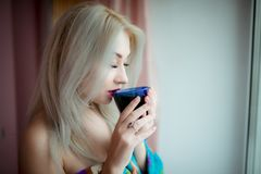 Blue-eyed blonde in a home dressing-gown near a window with a blue cup. This shot was made in bedroom near window in October,2016 in Kiev, Ukraine royalty free stock image