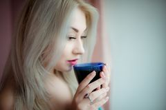 Blue-eyed blonde in a home dressing-gown near a window with a blue cup. This shot was made in bedroom near window in October,2016 in Kiev, Ukraine royalty free stock images