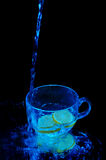Shot of water falling into a cup. On the black background Royalty Free Stock Photography