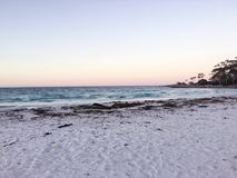 Sandy Beach with Calm Sea during the Sunset Time. A shot of a white sandy beach with a calm sea as a background - the sky appears to be soft pastel pink color Stock Image