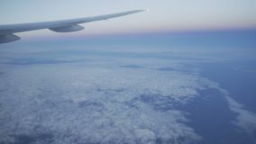 Shot of window of airplane. While flying above clouds at dusk stock video