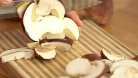 Shot of woman chef cutting mushrooms on chopping wooden board. 120 fps. stock footage