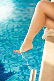 Shot of woman dangling sexy leg in swimming pool Stock Images