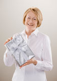 Shot of woman displaying classy wrapped gift. Studio shot of senior woman displaying classy wrapped gift Royalty Free Stock Photo