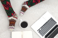 Shot of woman feet, laptop, coffee and notebook on the white car Stock Photography