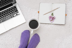 Shot of woman feet, laptop, coffee and notebook on the white car Stock Images