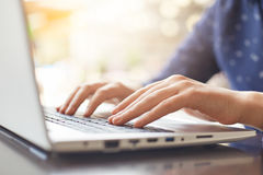 A shot of woman`s hands typing on keyboard while chatting with friends using computer laptop sitting at wooden table. People, life