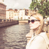 Shot of a woman standing a small bridge over the canal while on sightseeing in a foreign city. stock images