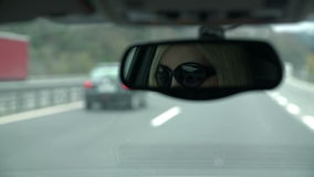 Shot of woman with sunglasses visible in rearview mirror driving towards tunnel. Blond female with sunglasses drives on the highway with the help of GPS in stock video