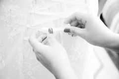 Shot of woman tying lace on bridal dress Stock Images