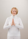 Shot of woman in white praying with hands clasped. Studio shot of senior woman in white praying with hands clasped Royalty Free Stock Photos
