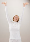 Shot of woman in white reaching with arms raised. Studio shot of senior woman in white reaching with arms raised Royalty Free Stock Images