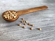 High angle shot of wooden spoon containing buckwheat buckinis Royalty Free Stock Images