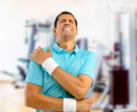 Injured sport man. Shot of a young athlete with a shoulder injury at gym royalty free stock photo
