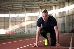 Young athlete at starting position ready to start a race.Sprinter ready for race. A Shot of young athlete at starting position ready to start a race.Sprinter Royalty Free Stock Image