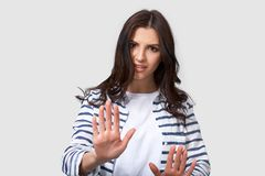 Shot of young brunette woman making stop gesture with her palms. Portrait of Caucasian female, making rejection gesture. Shot of young brunette woman making stop stock image