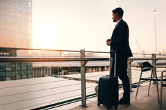 Businessman waiting for his flight in airport lounge. Shot of young businessman standing on airport lounge balcony with suitcase and looking outside. Man waiting Stock Images