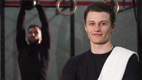Cheerful young sportsman smiling to the camera posing at the gym. Shot of a young cheerful attractive man smiling to the camera posing at the gym powerful stock footage