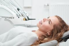 Young woman at the dentist office. Shot of a young cheerful woman waiting for medical examination at the dentist office sitting in a dental chair smiling looking royalty free stock photo