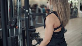 Shot of young fit woman doing biceps exercise using training machine in gym stock video