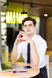 Shot of young man sitting at table looking at camera and thinking. Thoughtful businessman sitting home office. Sales man Stock Images