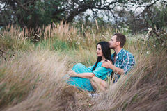 Shot of young man and woman sitting together outdoors on grass field. Royalty Free Stock Photography