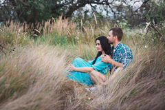 Shot of young man and woman sitting together outdoors on grass field. Royalty Free Stock Photo
