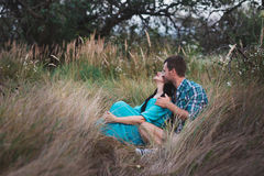 Shot of young man and woman sitting together outdoors on grass field. Royalty Free Stock Images