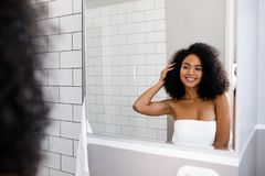 Shot of a young smiling woman deciding on a hair style. In front of a mirror Stock Photography
