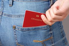 Shot of young woman behind in worn out jeans and passport in a pocket stock photo