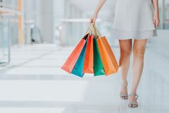 shot of young woman leg carrying colorful shopping bags royalty free stock image