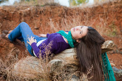Shot of a young woman lying on log Stock Images