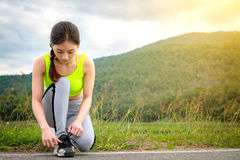 Shot of young woman runner tightening running shoe laces, getting ready for jogging exercise outdoors. Female jogger lacing her s stock photo