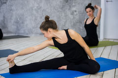 Shot of young women warming up before yoga session. Young people sitting on exercise mat in yoga class. Stock Photo